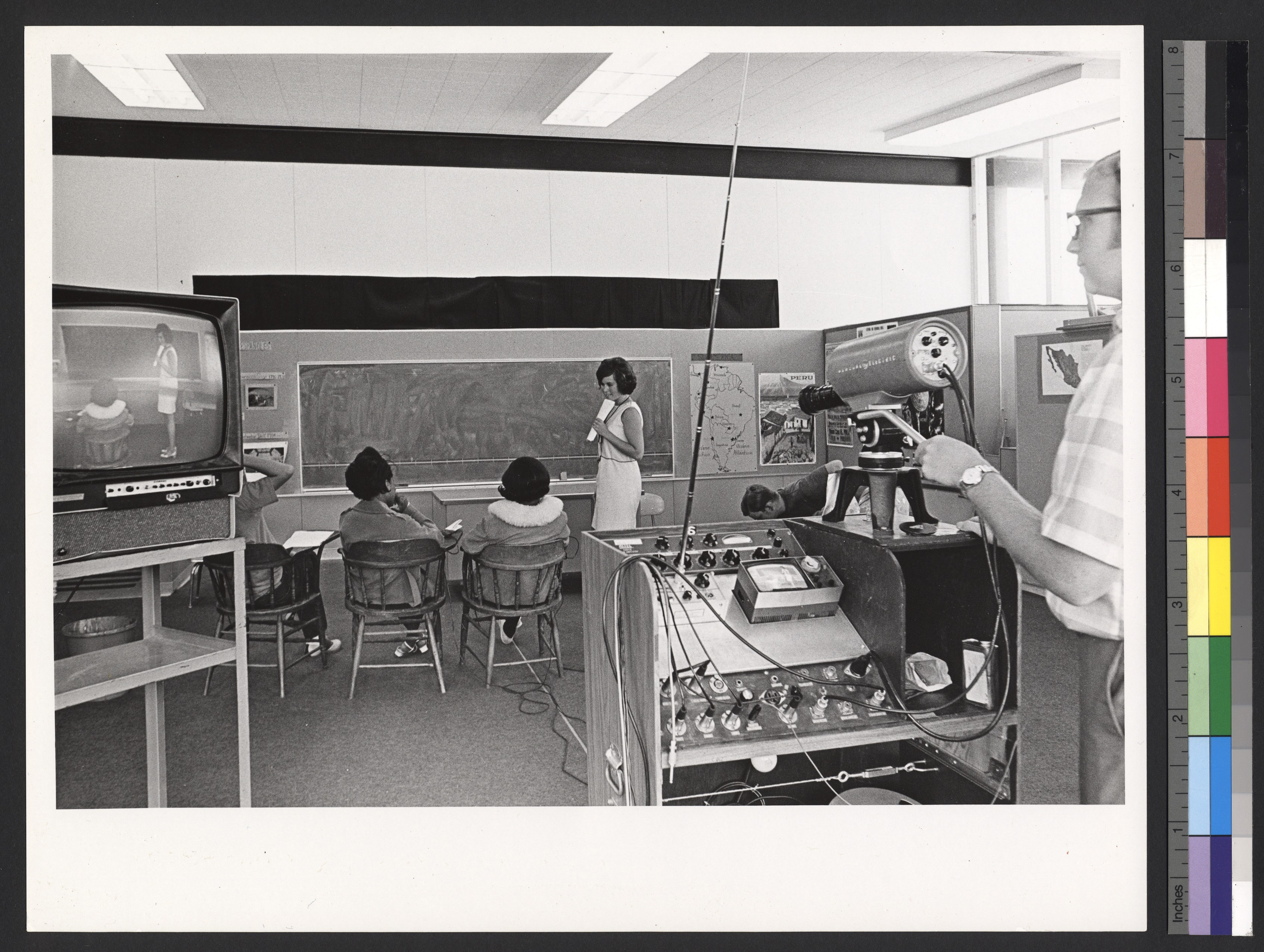 Black and white photo of old classroom being filmed with videotaping equipment.