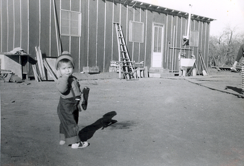 A small young boy in front of a shack.