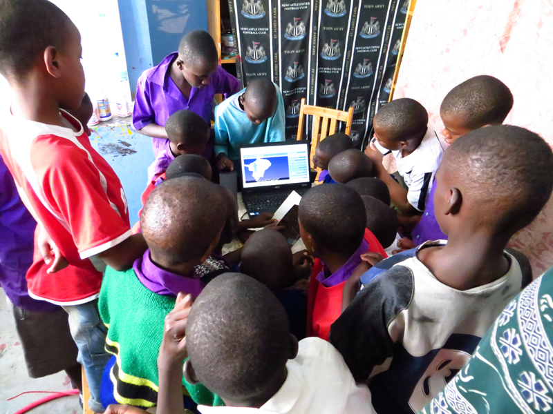 Students in Tanzania surrounding a laptop using TeachAIDS.