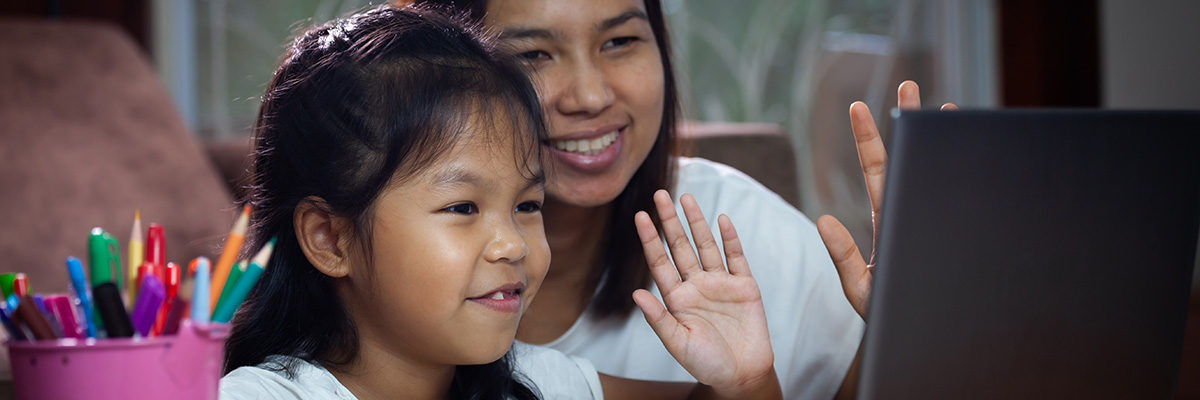 Photo of a mom and her daughter in front of a laptop waving.