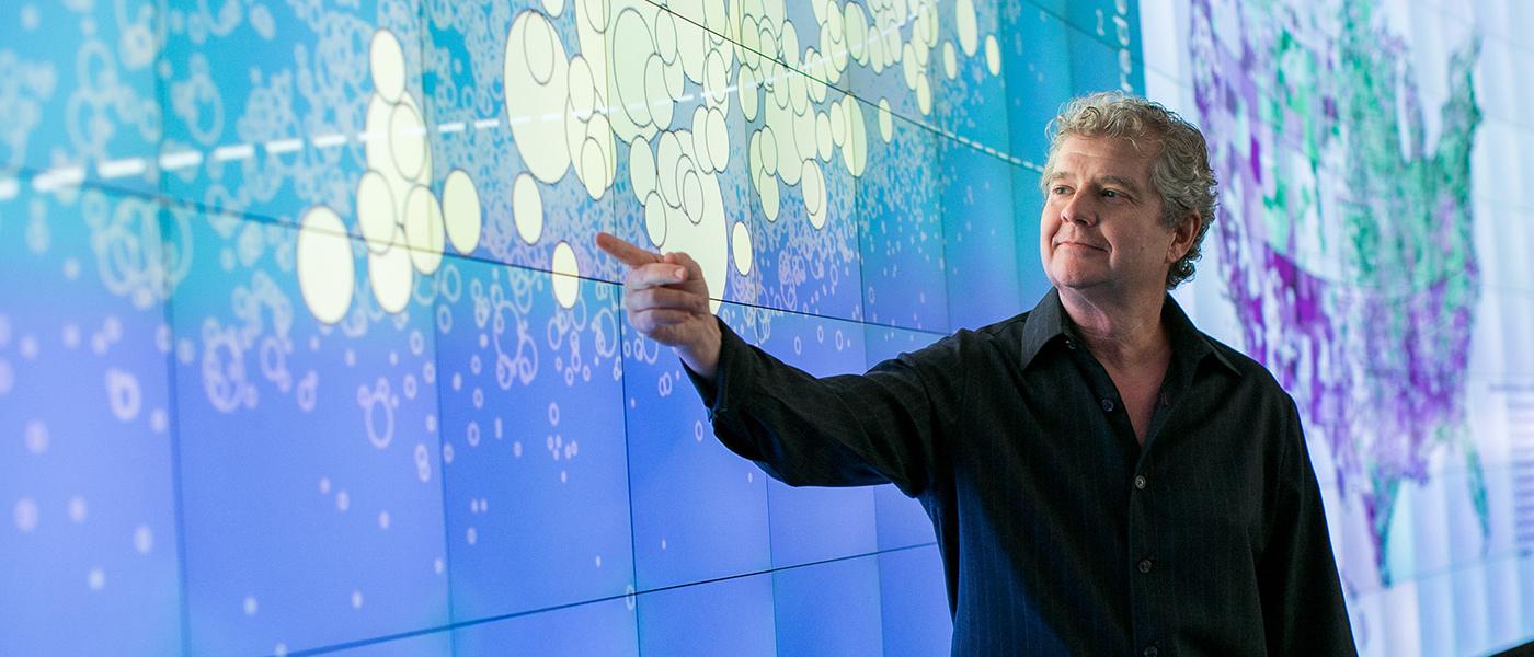 Photo of Sean Reardon pointing at a display