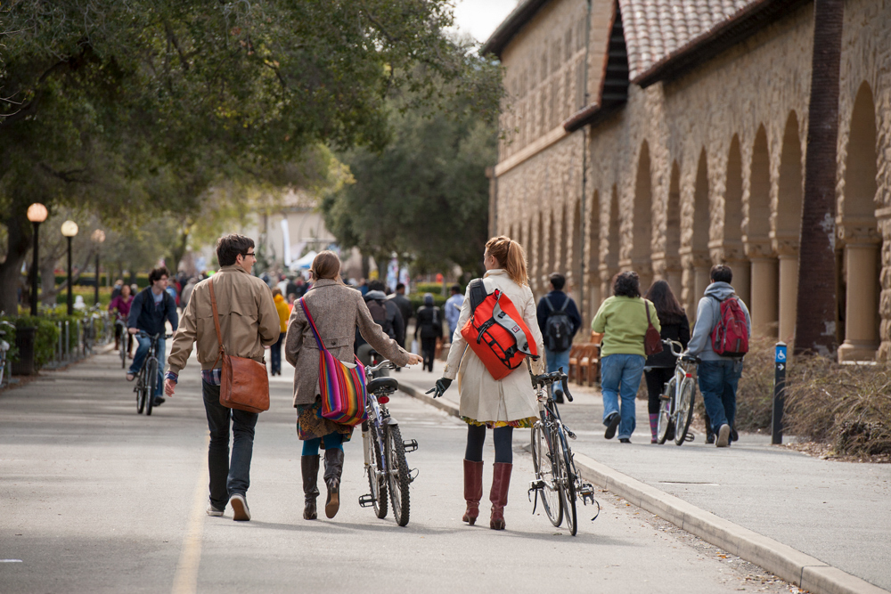 Photo of students riding and walking their bikes.