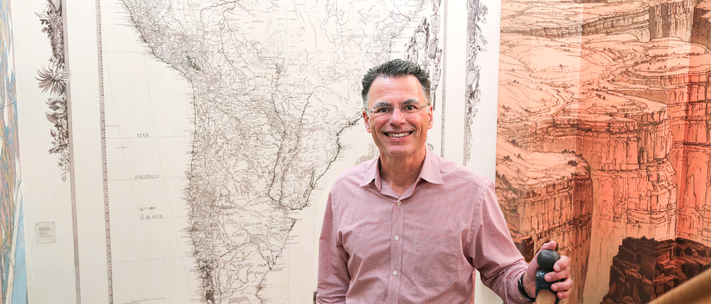 Photo of Christopher J. Thomas against a wall of maps