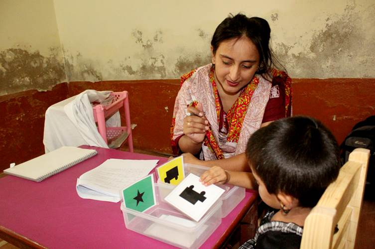 Assessor administers tests with preschooler in rural Pakistan