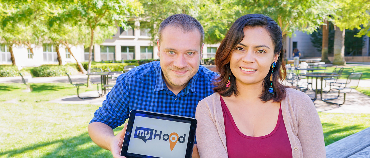 "A male and female student holding up their project logo ""myHood"""
