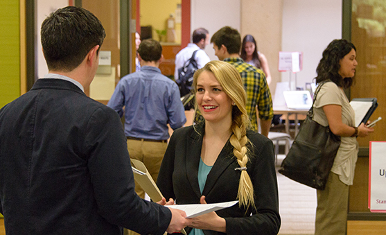 A GSE student (center) spoke with a potential employer on March 11 at a Stanford EdCareers job fair.