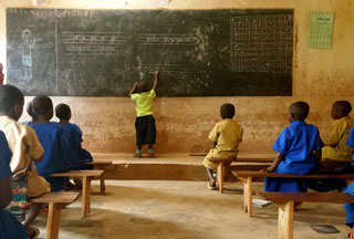A student practices writing at a school in the Gicumbi district in Rwanda (Photo by Saima Malik)