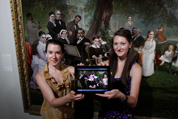 Renee Bruner (left) and Meredith Downing display the app they created as they stand in front of Thomas Hill's painting Palo Alto Spring depicting Leland Stanford Jr's 10th birthday. (Photo: Paul Sakuma)