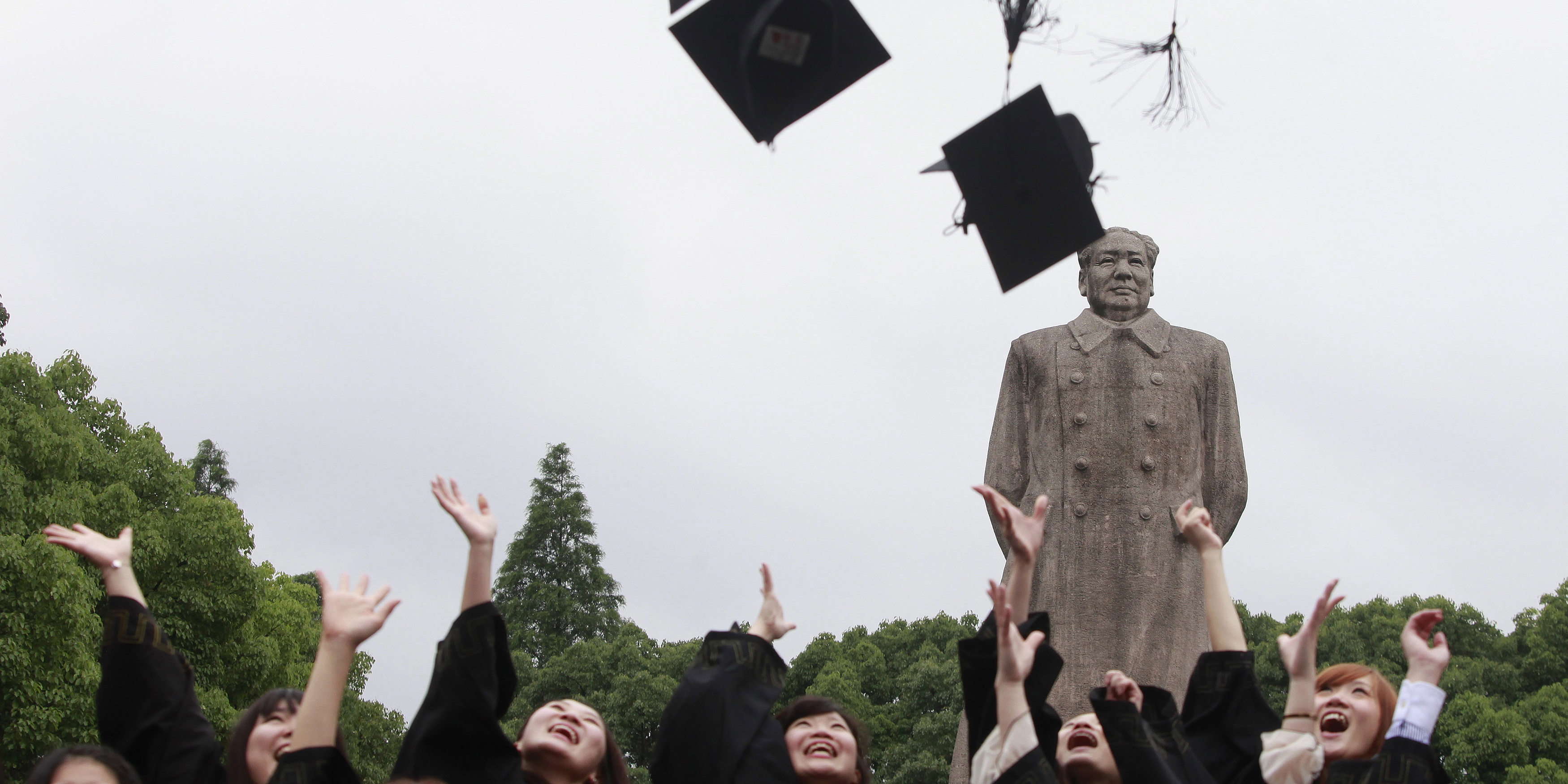 Graduates from Fudan University in Shanghai celebrate in front of the statue of late Chinese leader Mao Zedong on June 28, 2013.  Photo credit: Reuters