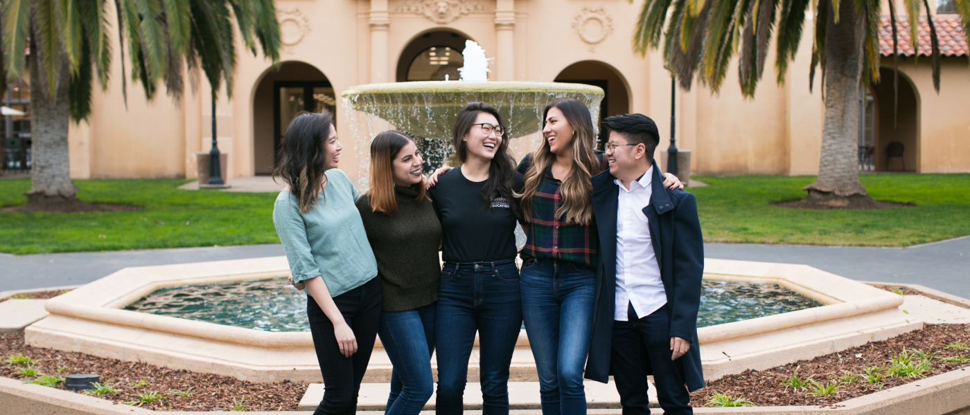Photo of a group of students laughing in front of a water fountain.
