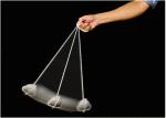 A person swinging a rock pendulum.