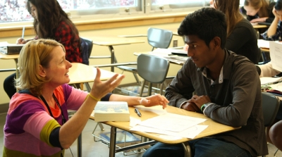 A teacher kneels down to talk with an English language learning student about an essay he is writing.