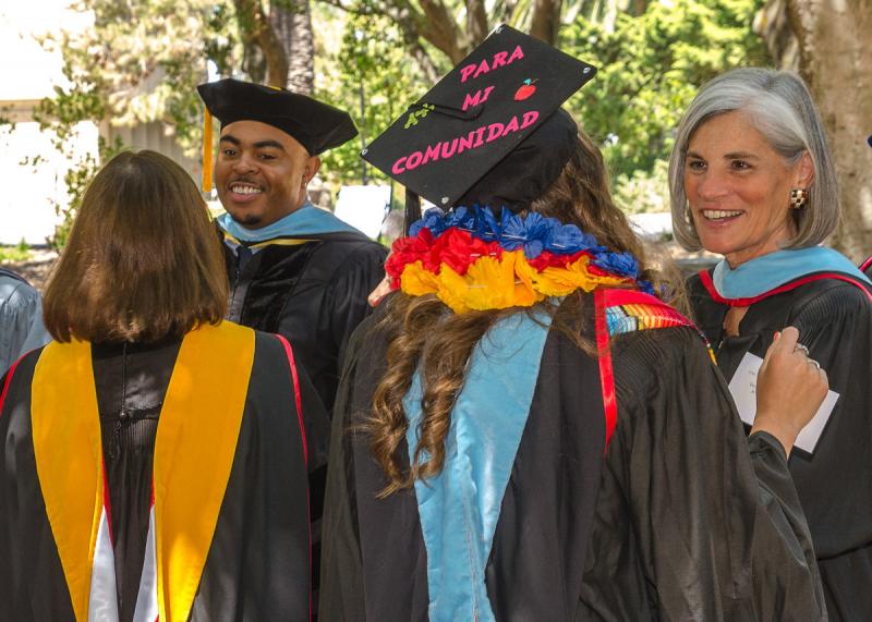 Graduates speaking with professors.