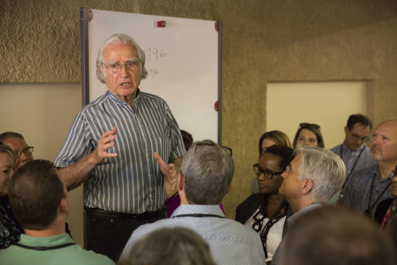 Lecturer speaking to a surrounding group of adults