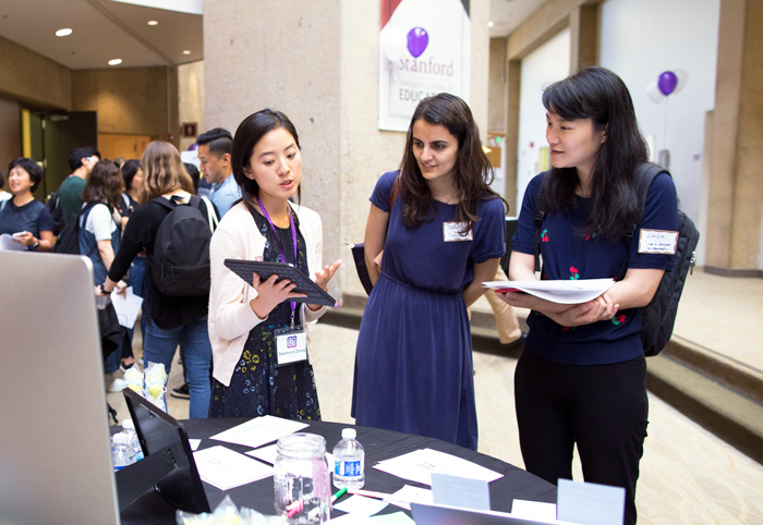 A female student presenting their project on a tablet to two female attendees.
