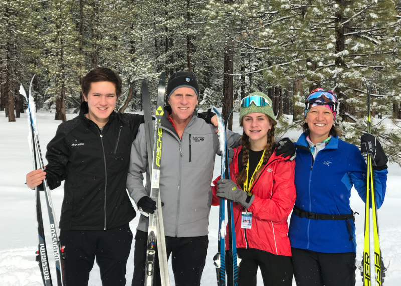 A family posing for a picture with ski on a snowy background