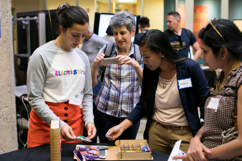 Eileen Rivera (left) shows attendees how to use ElectriStitch, a kit that guides children through the fundamentals of electronic circuits, sewing, design and computation.