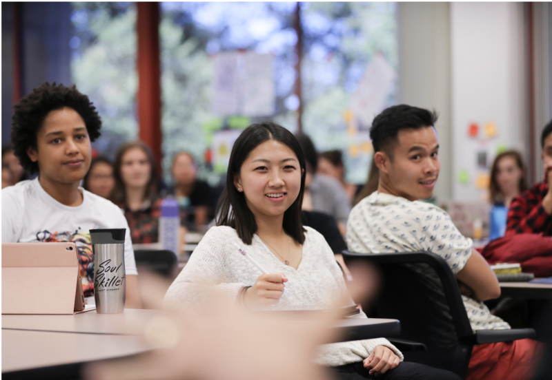 Female student at the table smiling.