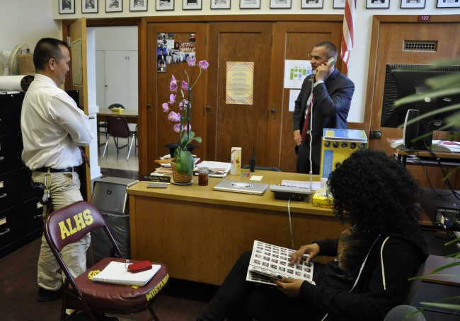 Barnaby Payne (center) works in his office at Abraham Lincoln High School (Photo by Brooke Donald)