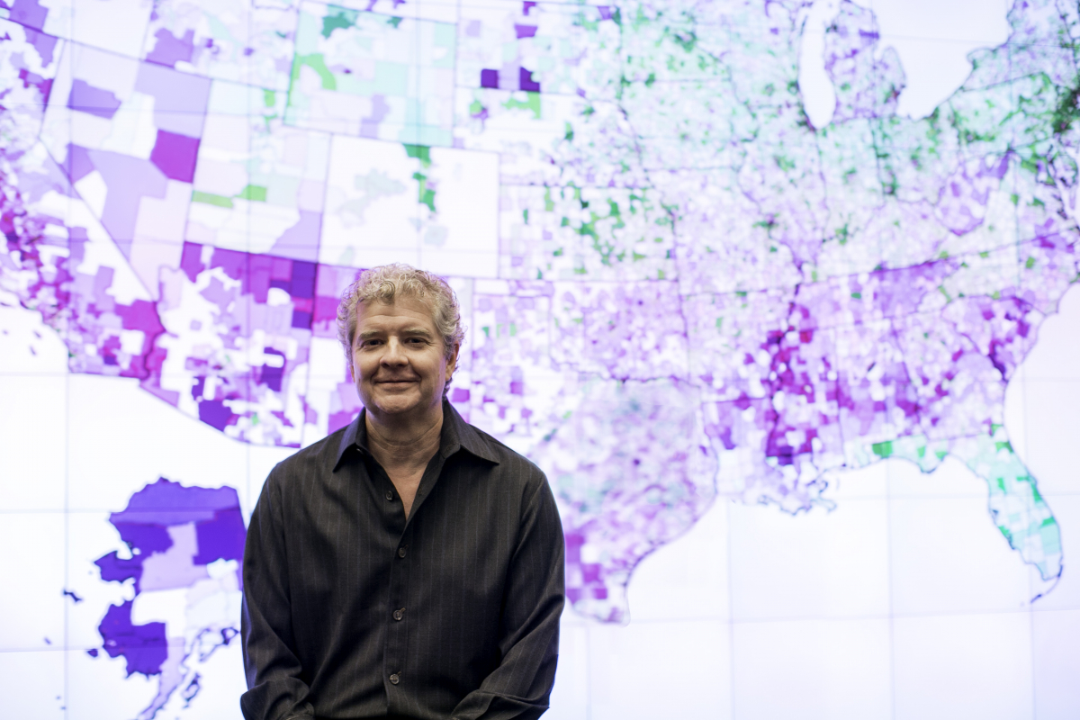Photo of Sean Reardon in front of U.S. map showing school achievement data