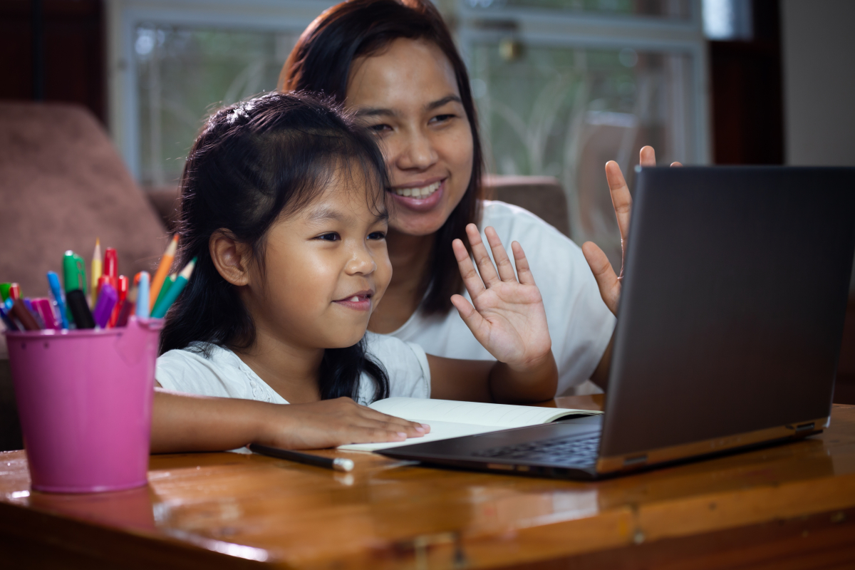 Photo of mother helping child with remote learning