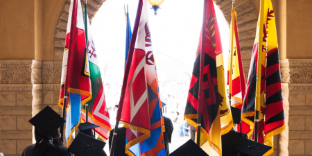 Image in color that shows graduates holding the flags of Stanford's seven different graduate and professional schools
