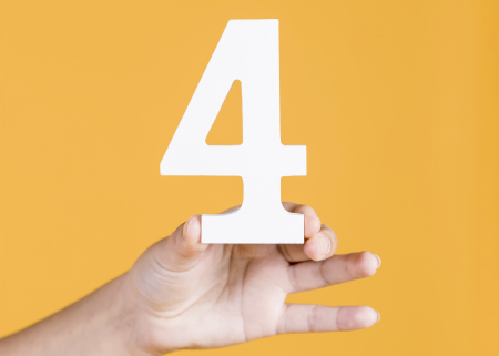 Woman's hand holding up the number 4 against an yellow background