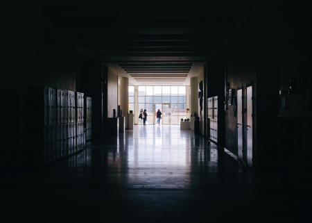 Photo of a dark school hallway opening into the light