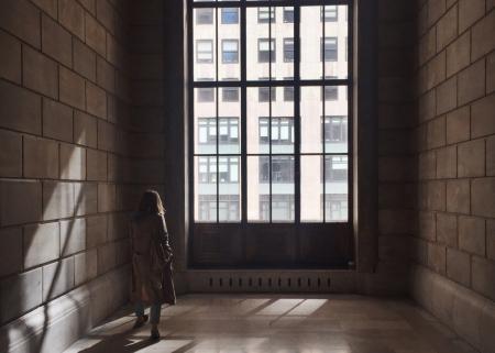 A lone student walks down a dark corridor toward a window