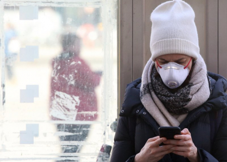 A young woman wearing a mask uses her smartphone