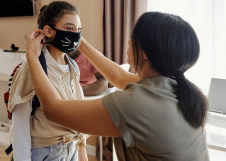 A mother putting a mask on a child ready to head to school