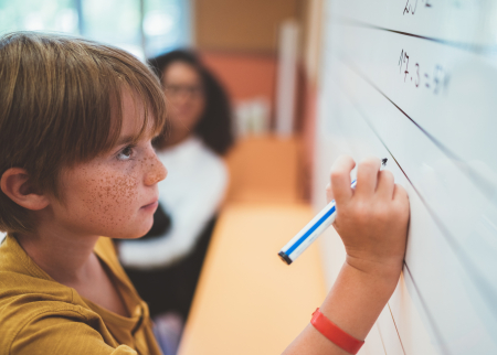 Photo of child doing math problem on a white board