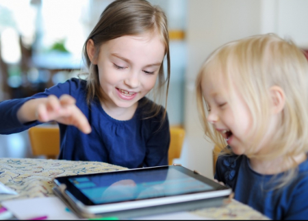 Two young girls playing on an iPad together