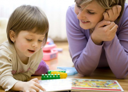Photo of child working on a puzzle with a parent