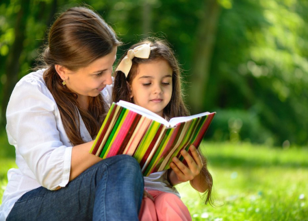 Mom is reading a book with her daughter outside