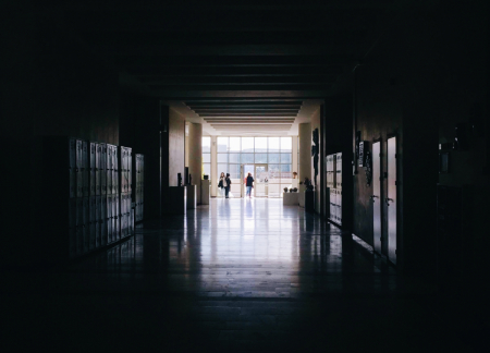 A darkened school hallway with students in the far distance