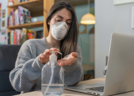 Teenager with a mask using hand sanitizer