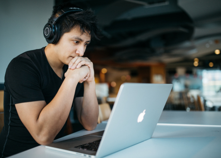 A student at a laptop with headphones on