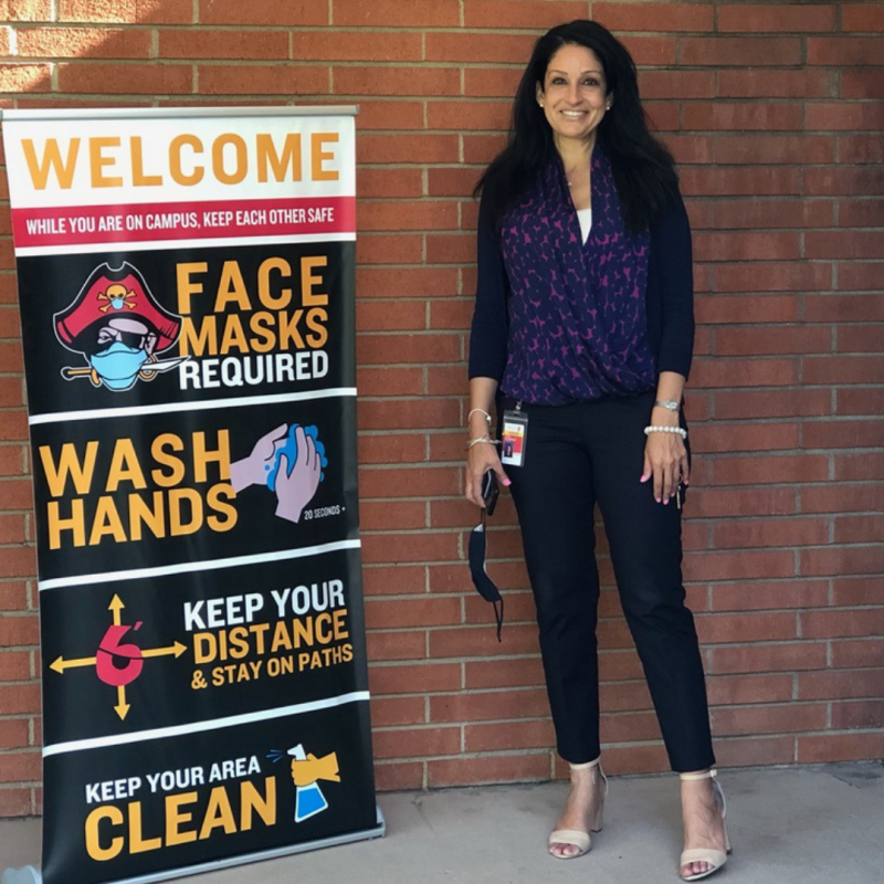 Photo of Facia Desmond at her school, standing near a sign that welcomes students and gives guidance about how to keep others safe during COVID