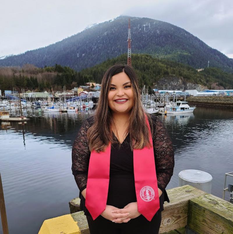 Photo of Jeanette Kaleikau-Buxton in Alaska, wearing her Stanford graduation stole