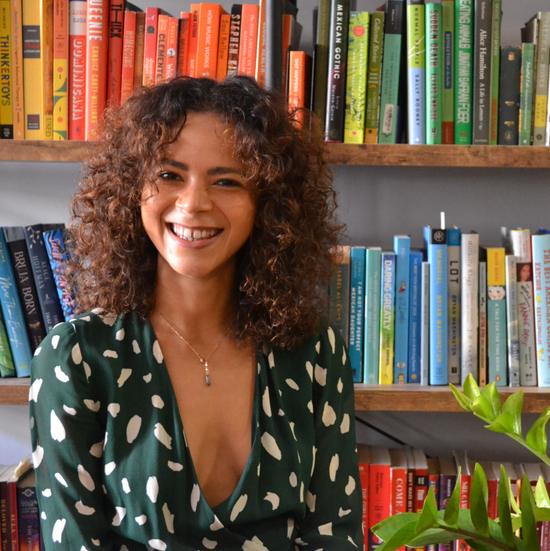 Kia Turner smiling in front of beautifully colorful books