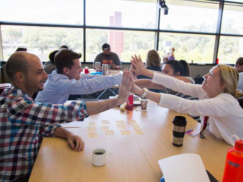 Photo of people around the table give a group high-five