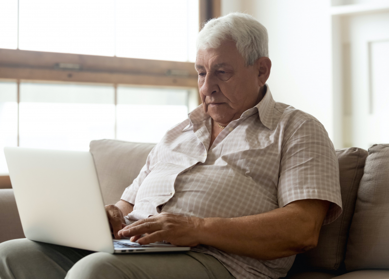Photo of older man on a computer