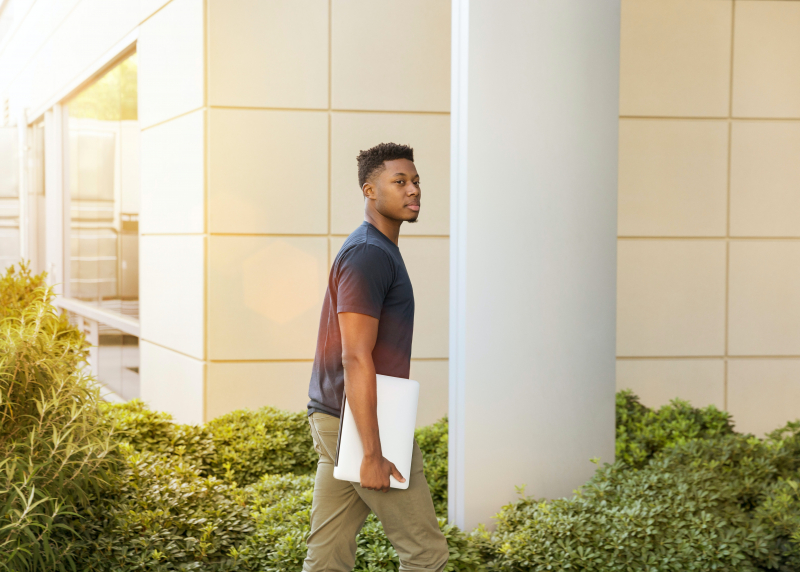 Photo of a young black man with a laptop walking into a building