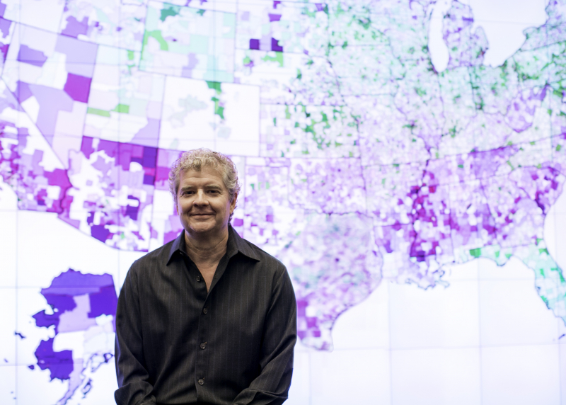 Photo of Sean Reardon in front of U.S. map showing school achievement data