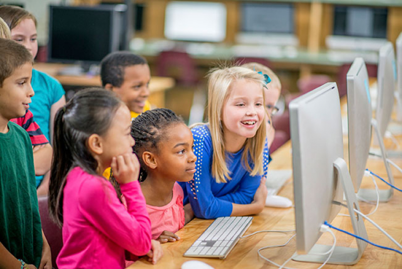 Children with computers in classroom (© Christopher Futcher, iStock)