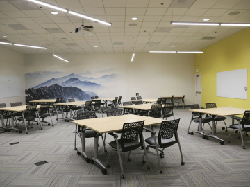Image of a big room with table, chairs and whiteboards