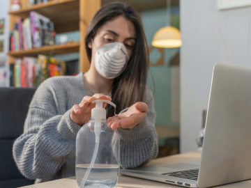 Photo of woman watching video, wearing mask and using hand sanitizer