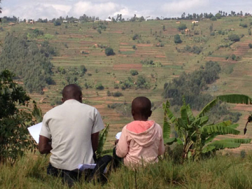 A young student takes a reading assessment in the hills of the Gicumbi district in rural Rwanda (Photo by Elliott Friedlander)