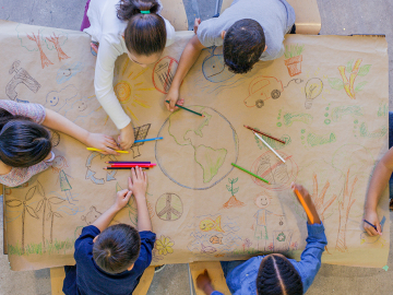 children drawing the earth on a large table